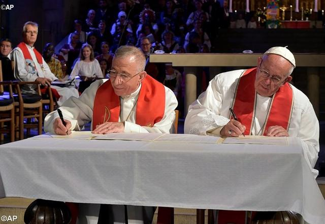 Pope Francis and Bishop Mounib Younan sign the Joint Statement in Lund's Cathedral - AP